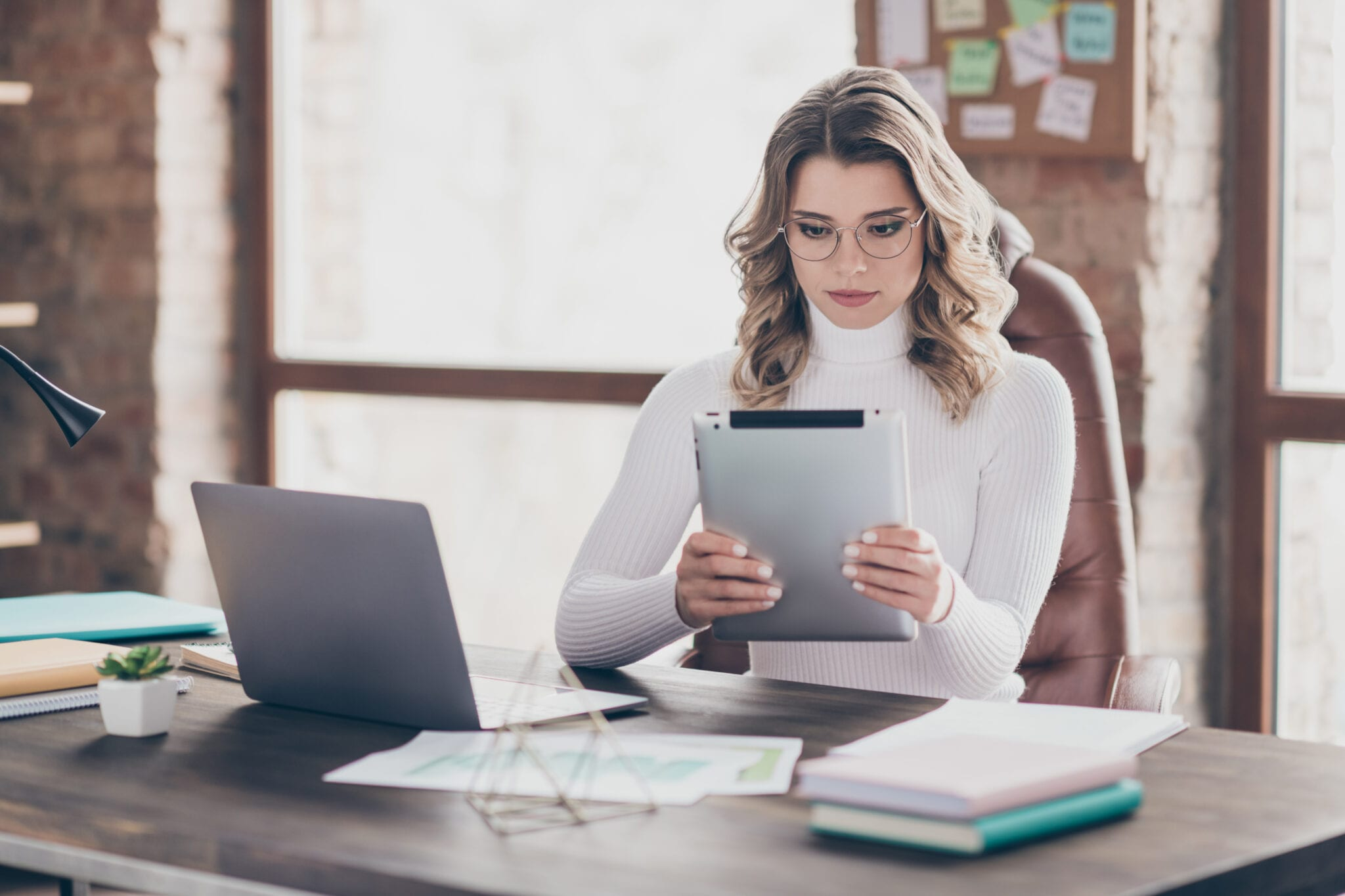 A woman sitting at her desk researching stock market blogs.